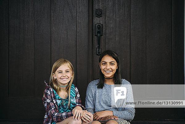 Porträt von Freunden  die an der Tür sitzen