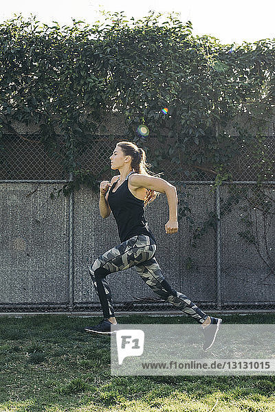 Full length side view of determined female athlete running at park