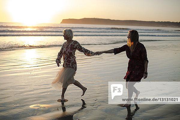 Verspielte Mutter und Tochter in voller Länge  die sich bei Sonnenuntergang am Strand gegen den Himmel vergnügen
