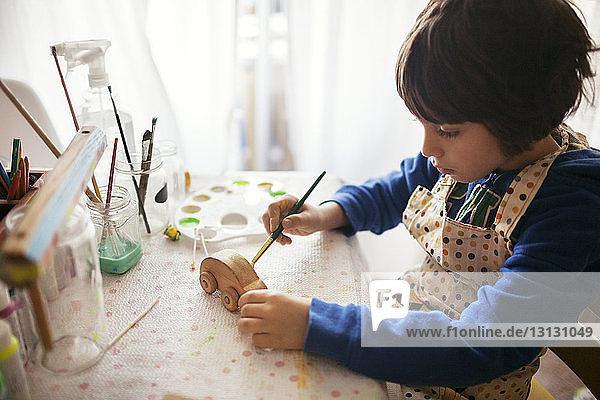 Junge malt hölzernes Spielzeugauto am Tisch