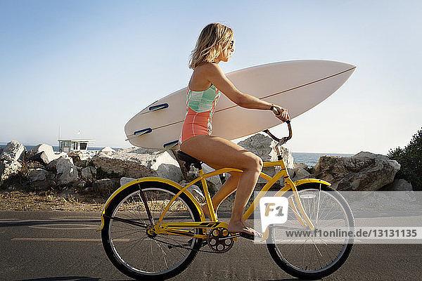 Seitenansicht einer Frau mit Surfbrett beim Fahrradfahren auf der Straße am Strand Seitenansicht einer Frau mit Surfbrett beim Fahrradfahren auf der Straße am Strand