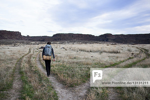 Rear view of hiker with backpack walking on field against sky