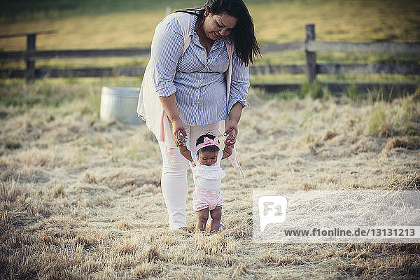 Mutter hilft Tochter beim Gehen auf Grasfeld auf Ranch