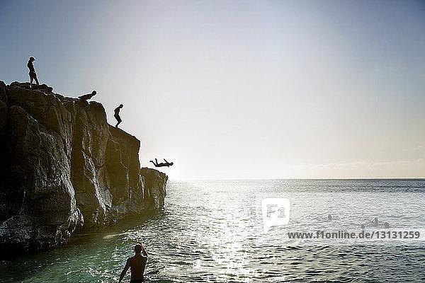 Freunde springen von Klippe zu Meer gegen Himmel