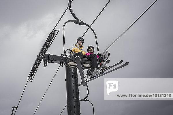 Niedrigwinkelansicht eines Vaters mit Tochter  der auf einem Skilift sitzt  vor bewölktem Himmel im Winter
