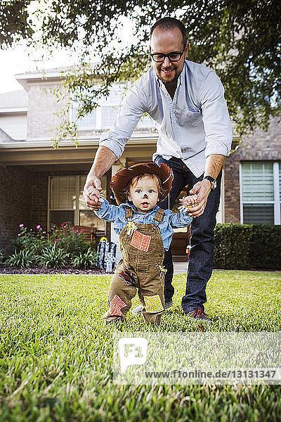 Vater hält als Cowboy verkleideten kleinen Jungen im Hinterhof