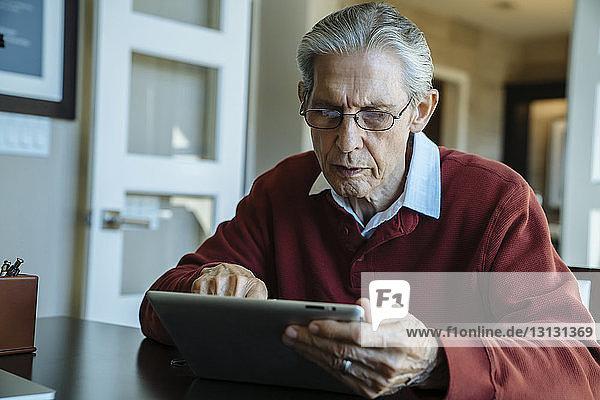 Senior man using tablet computer in financial advisor's office
