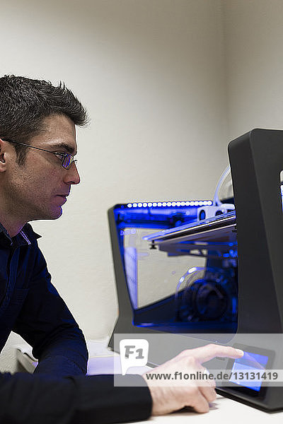 Engineer operating 3D printer on table in office