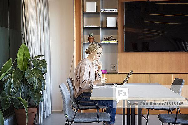 Seitenansicht einer Geschäftsfrau  die im Büro am Tisch arbeitet