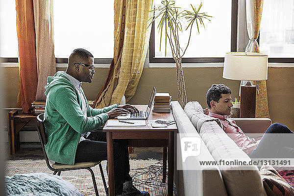 Side view of gay man using laptop at table while partner sitting on sofa