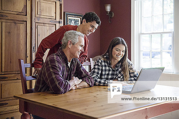 Family looking at laptop computer at home