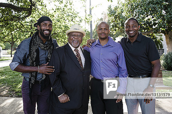 Porträt eines glücklichen Vaters mit Söhnen im Park stehend