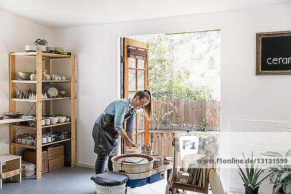 Frau mischt Ton in Eimer in Töpferwerkstatt