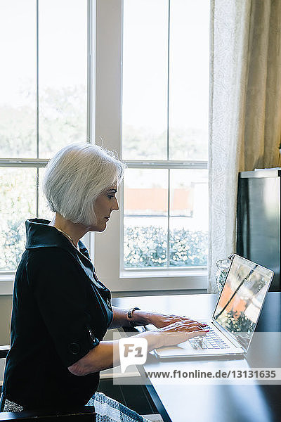 Side view of businesswoman using laptop computer while sitting against window in office
