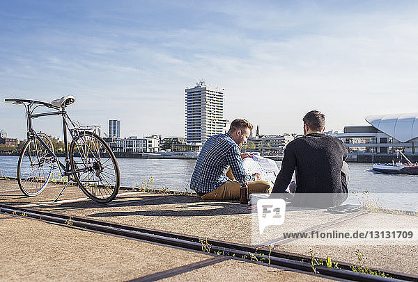 Friends looking at document while sitting by bicycle on promenade against clear sky