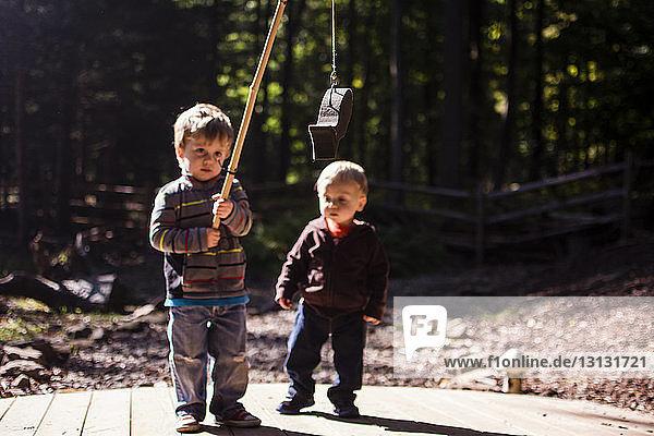 Junge sieht Bruder an  der künstliche Fische auf dem Spielplatz hält