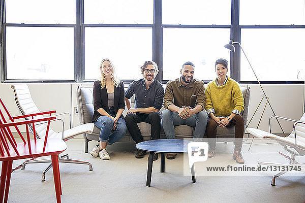 Porträt von lächelnden Geschäftsleuten  die im Büro auf dem Sofa sitzen