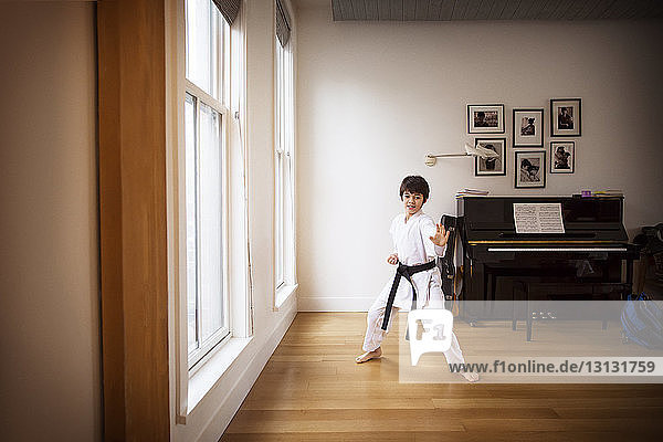 Boy practicing karate by window at home