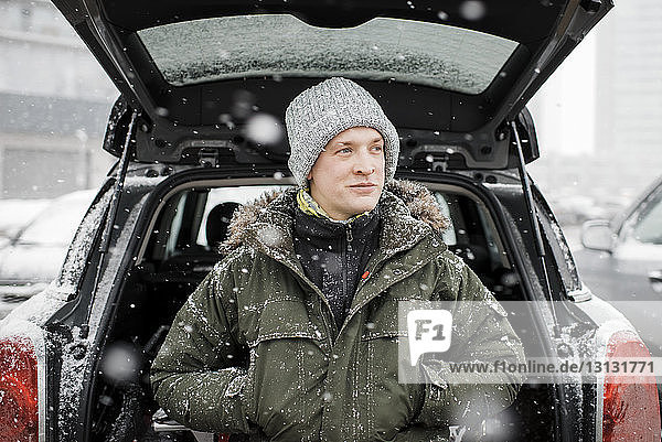 Man looking away while standing by car trunk during snowfall