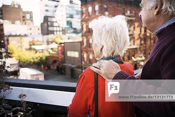 Älteres Ehepaar betrachtet die Stadtansicht  während es auf dem Balkon steht