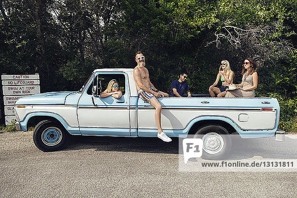 Cheerful friends enjoying while sitting in pick-up truck