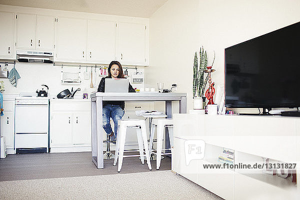 Businesswoman using laptop computer while working in home office