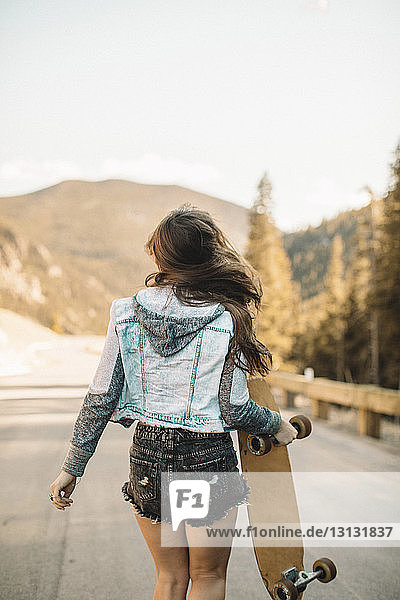Rear view of young woman with skateboard standing on road against mountains