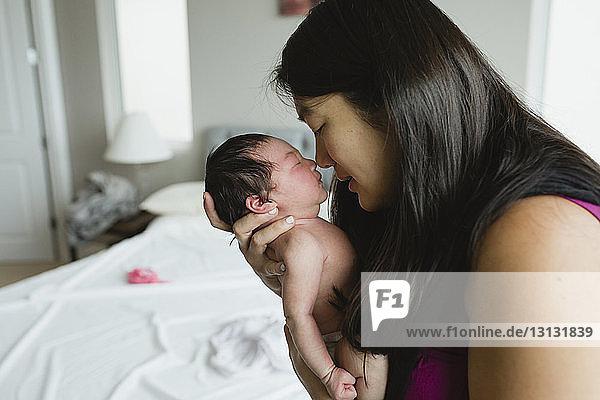 Nahaufnahme einer Mutter  die eine neugeborene Tochter trägt  während sie zu Hause im Schlafzimmer steht