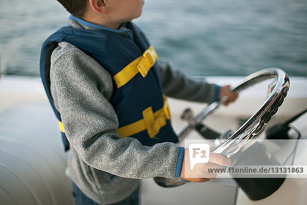 Boy holding steering wheel on boat