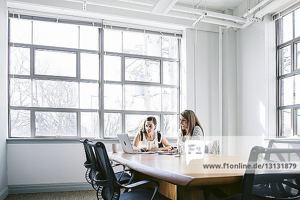 Female colleagues planning in board room at office