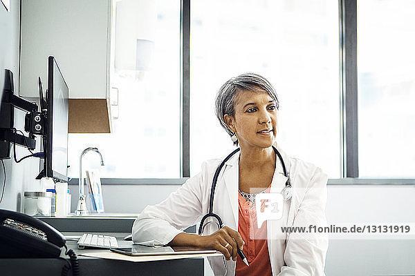 Zuversichtliche Ärztin am Schreibtisch in der Klinik