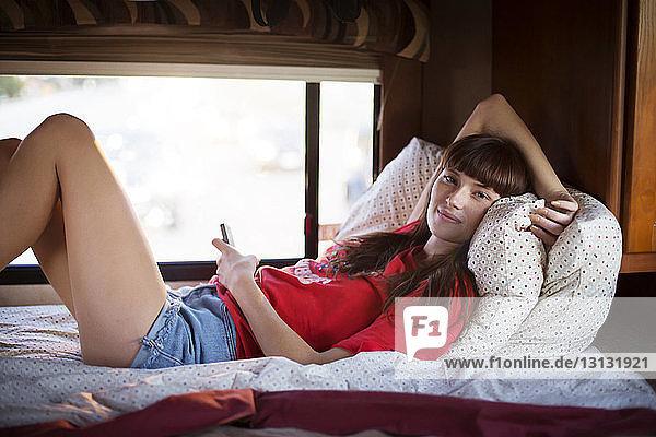 Porträt einer Frau  die ein Smartphone in der Hand hält  während sie sich im Bett im Wohnmobil entspannt