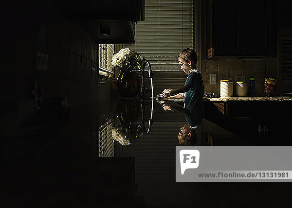 Boy washing container in kitchen at home