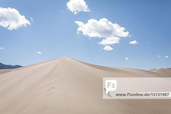 Hochwinkelaufnahme einer Frau  die am sonnigen Tag auf eine Sanddüne im Nationalpark klettert