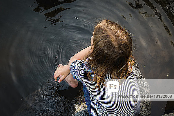 Overhead view of girl sitting on rock in lake