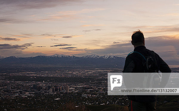Silhouetten-Mann steht gegen Stadtbild