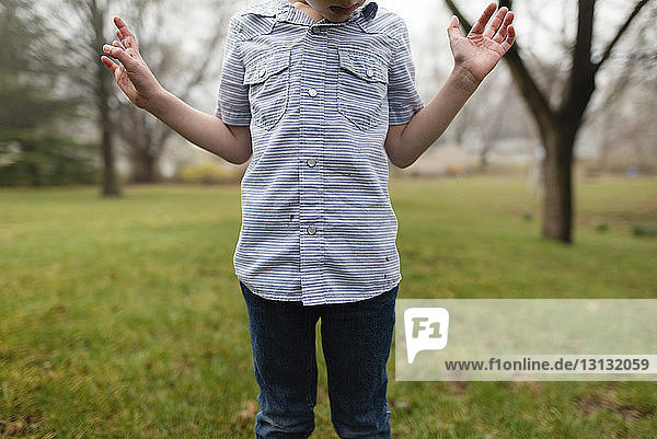 Midsection of boy standing on grassy field in park