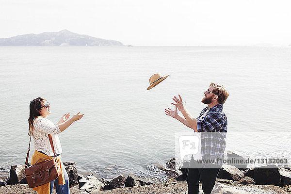 Paar spielt mit Hut  während es gegen das Meer steht