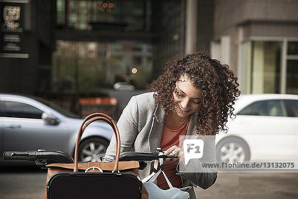 Glückliche Geschäftsfrau mit Fahrrad auf der Straße