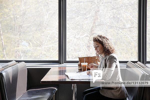 Seitenansicht einer Geschäftsfrau beim Lesen einer Zeitschrift im Cafe
