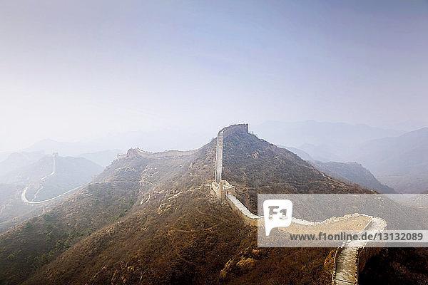 Chinesische Mauer und Berge bei nebligem Wetter gegen den Himmel