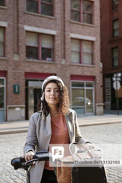 Porträt einer selbstbewussten Geschäftsfrau  die auf der Straße ein Fahrrad hält