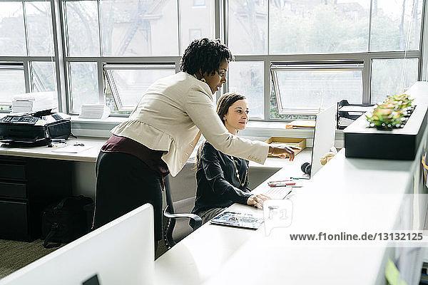Geschäftsfrau zeigt auf Desktop-Computer  während sie mit einem Kollegen spricht