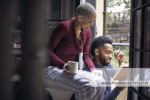 Glückliche Frau  die ihrem Freund beim Lesen eines Buches zusieht  während sie an der Tür sitzt