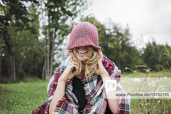 Fröhliche Frau  die mit Strickmütze die Augen bedeckt  während sie auf dem Feld vor Bäumen steht