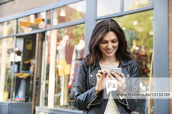 Glückliche Frau benutzt Smartphone vor dem Geschäft