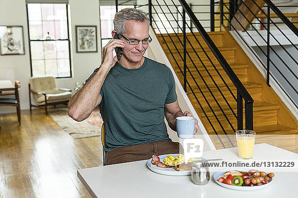 Reifer Mann hält Kaffeetasse in der Hand  während er am Esstisch an ein Smartphone geht