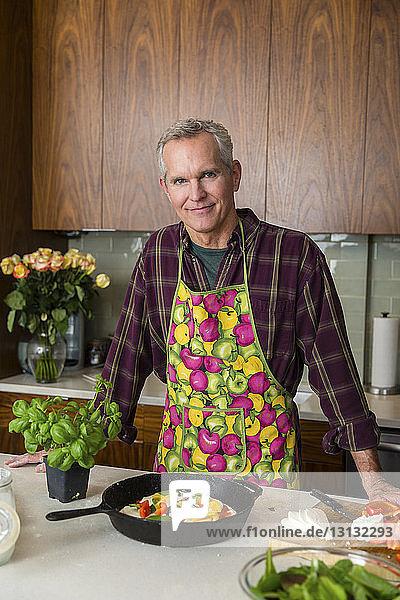 Porträt eines selbstbewussten reifen Mannes  der zu Hause in der Küche Pizza zubereitet
