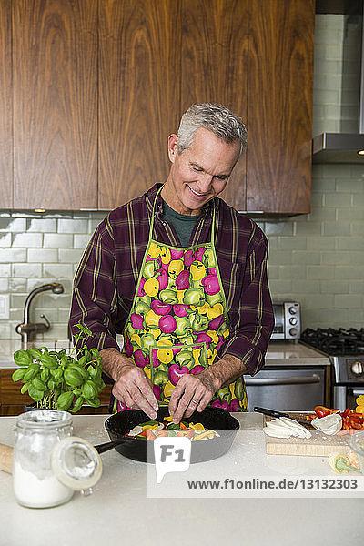 Lächelnder reifer Mann bereitet zu Hause in der Küche Pizza zu
