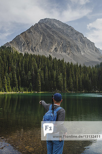 Rear view of hiker with backpack pointing towards lake while standing against mountains at forest